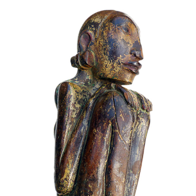 Bali female anamist figure of slender form and seated in a typical hunkerred position