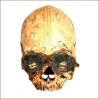 Dayak human trophy skull with finely carved cranial area and eyes set with pitch